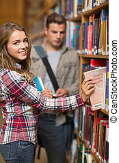 sonriente, estudiante, toma, libro, de, estante, en, biblioteca