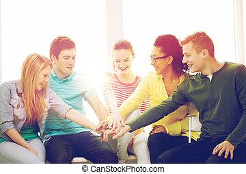 sonriente, estudiantes, con, manos, cima, de, uno al otro