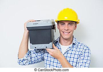 sonriente, factótum, en, sombrero duro amarillo, proceso de llevar, caja de herramientas