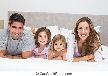 sonriente, familia , en cama