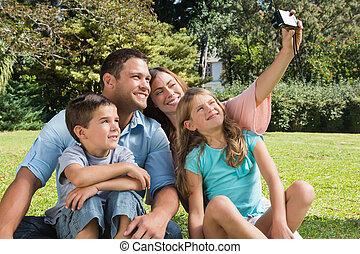 sonriente, familia , en, un, parque, tomar las fotos