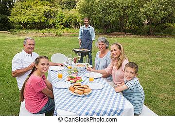 sonriente, familia extendida, tener una barbacoa