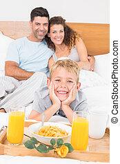 sonriente, familia joven, teniendo, desayuno en cama