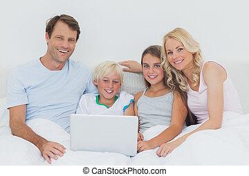 sonriente, familia , utilizar, un, computador portatil, juntos