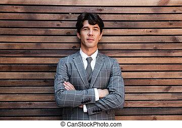 sonriente, guapo, hombre de negocios, en, traje, posición, con, brazos doblados