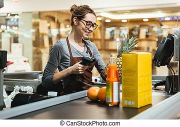 sonriente, hembra, cajero, exploración, tienda de comestibles, artículos