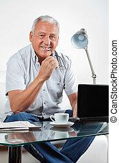 sonriente, hombre mayor, con, computador portatil, en, tabla