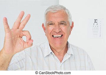 sonriente, hombre mayor, el gesticular, aprobar, con, eye la carta, en, plano de fondo