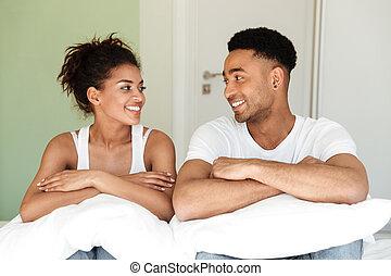 sonriente, joven, africano, par cariñoso, el sentarse en cama