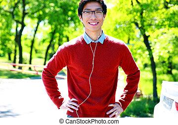 sonriente, joven, escuchar música, en el parque