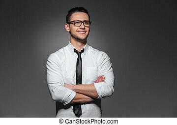 sonriente, joven, hombre de negocios, en, anteojos, posición, con, armamentos cruzaron