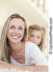 sonriente, madre e hija, sobre el piso
