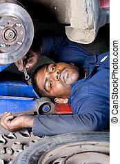 sonriente, mecánico, trabajando, debajo, coche