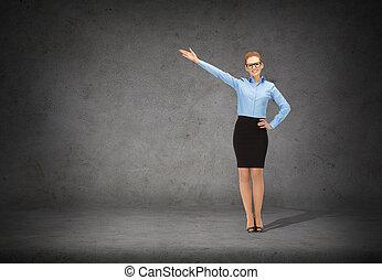 sonriente, mujer de negocios, en, anteojos, señalar, ella, mano