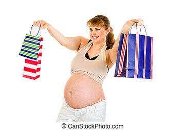 sonriente, mujer embarazada, tenencia, bolsas de compras, en, manos, aislado, blanco