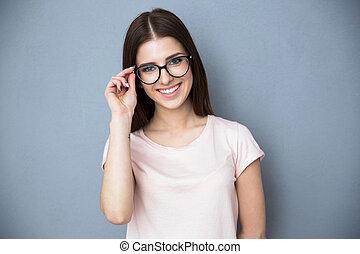sonriente, mujer joven, con, anteojos, encima, fondo gris