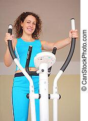 sonriente, mujer joven, en, entrenamiento, aparato