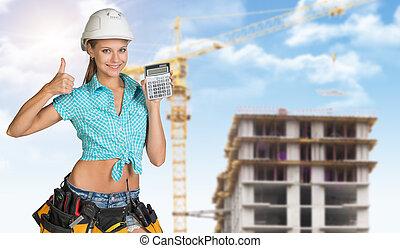 sonriente, mujer joven, en, sombrero duro, tenencia, calculadora