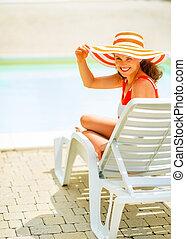 sonriente, mujer joven, en, sombrero, sentado, en, sunbed