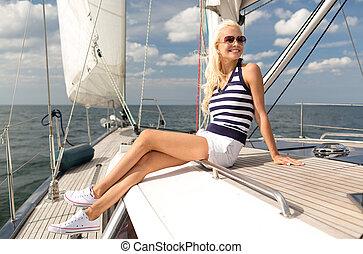 sonriente, mujer joven, sentado, en, yate, cubierta