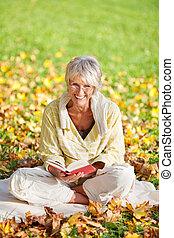 sonriente, mujer mayor, libro de lectura, en el estacionamiento