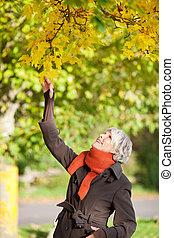 sonriente, mujer mayor, tenencia, rama de árbol