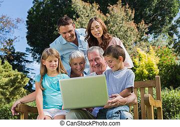 sonriente, multi, generación, familia , con, un, computador portatil, sentado, en el estacionamiento
