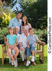 sonriente, multi, generación, familia , sentado, en, un, banco, en el estacionamiento