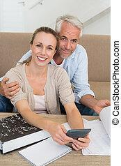 sonriente, pareja, calculador, su, cuentas, en, el, sofá