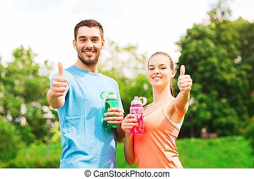 sonriente, pareja, con, botellas, de, agua, aire libre