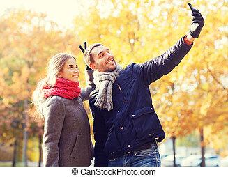 sonriente, pareja, con, smartphone, en, otoño, parque
