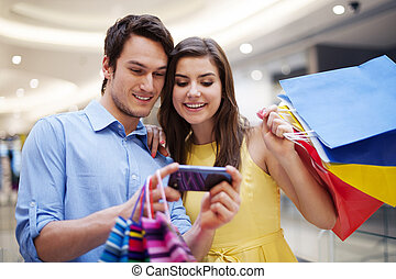 sonriente, pareja, el mirar, teléfono móvil