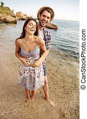 sonriente, pareja, enamorado, posición, en la playa, y, abrazar