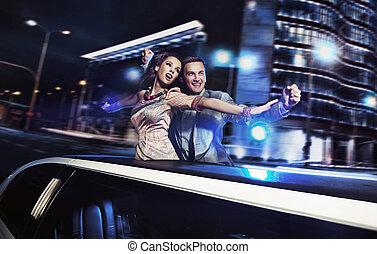 sonriente, pareja, encima, noche, ciudad, plano de fondo