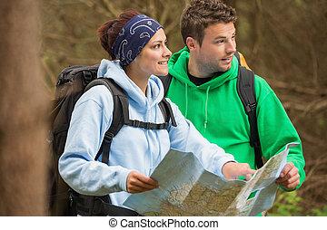 sonriente, pareja, posición, en, un, bosque, tenencia, mapa