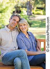 sonriente, pareja, sentado, en, parque