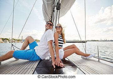 sonriente, pareja, sentado, en, yate, cubierta