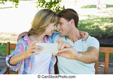 sonriente, pareja, sentar banco, en el parque, toma, un, selfie
