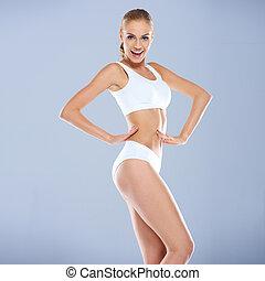 sonriente, sexy, mujer joven, en, blanco, condición física, equipo