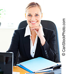 Sophisticated caucasian businesswoman smiling at the camera in her office at her desk