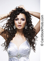 Sophistication. Fashionable Woman with Frizzy Hair with Earrings. Curly Hairstyle