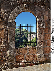 Sorano, Grosseto, Tuscany, Italy: ancient window in the alley to the fortress Masso Leopoldino in the old town of the medieval Tuscan village