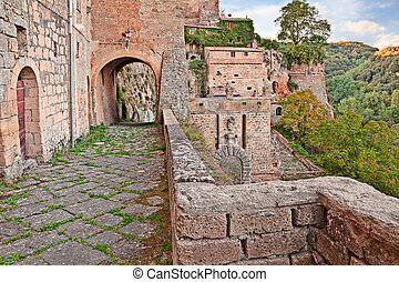 Sorano, Grosseto, Tuscany, Italy: walkway on the walls of the medieval town with the city gate Porta dei Merli at the bottom