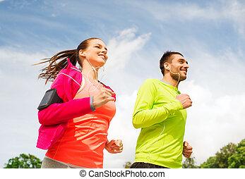 sorridente, coppia, con, auricolari, correndo, fuori