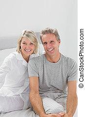 sorridente, coppia, sedendo letto
