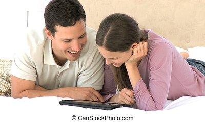 sorridente, coppia, usando, uno, computer, tavoletta, mentre, loro, ara, dire bugie