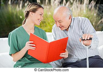 sorridente, dall'aspetto, mentre, libro, femmina, anziano, lettura, infermiera, uomo