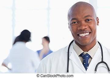sorridente, dottore, standing, con, suo, stetoscopio, intorno, suo, collo