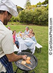sorridente, famiglia estesa, avendo barbecue, essendo, cotto, vicino, padre, in, cappello chef, esterno, in, sole