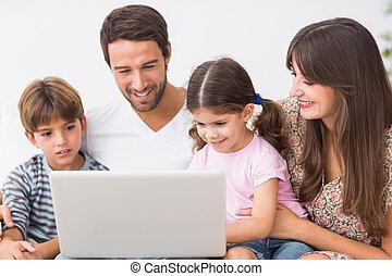 sorridente, famiglia, usando computer portatile, su, divano